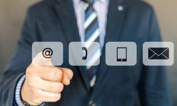 Des icônes de contacts (téléphone, mail, ...) où un homme en arrière plan pointe son doigt sur l'icone du mail