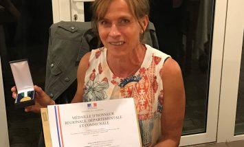 Isabelle Doyen reçoit un diplôme et une médaille d'honneur.
